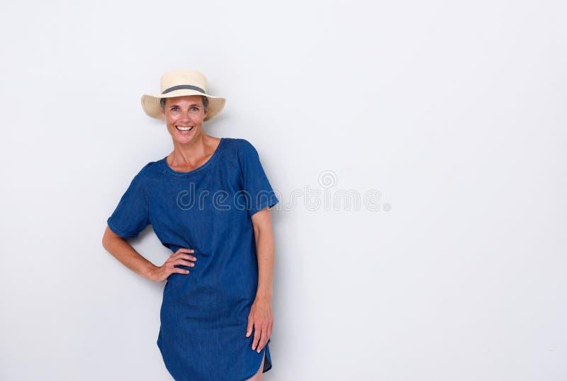 Härlig äldre kvinna som ler med hatten mot vit bakgrund royaltyfri fotografi
