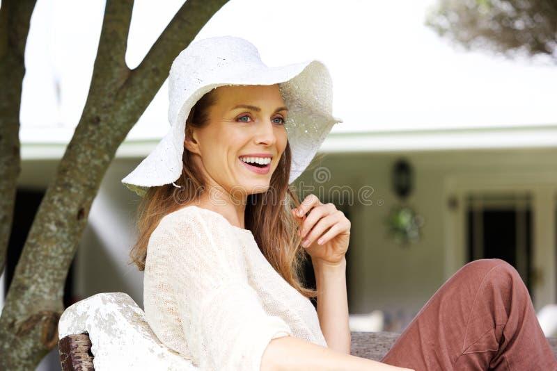 Härlig äldre kvinna som ler med solhatten fotografering för bildbyråer