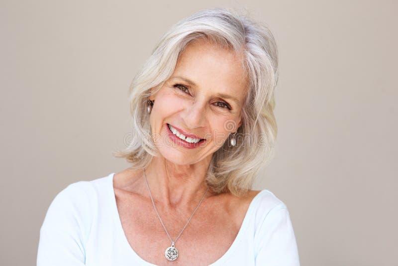 Härlig äldre kvinna som ler och står vid väggen fotografering för bildbyråer