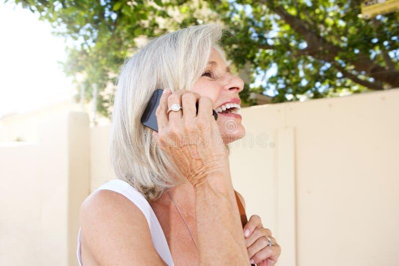 Härlig äldre kvinna som utanför talar på mobiltelefonen fotografering för bildbyråer