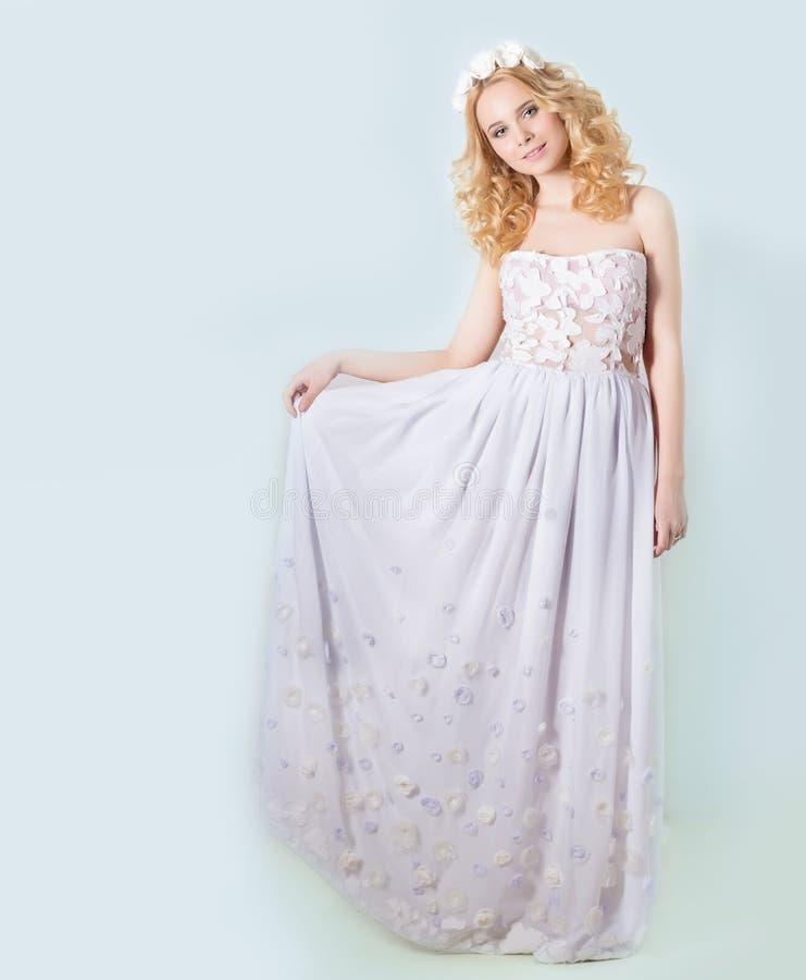 Härlig älskvärd försiktig elegant ung blond kvinna i en vit sundresschiffong och krullning och en krans av blommor i hennes hår arkivbild