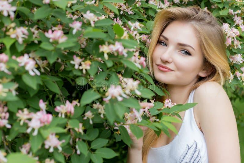 Härlig älskvärd flicka med långt blont hår som tycker om naturen nära blommande rosebush i en vit t-skjorta med ljus sommar för f fotografering för bildbyråer