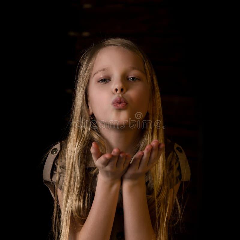 Härlig älskvärd liten blond flicka med olika sinnesrörelser på en mörk bakgrund arkivbilder