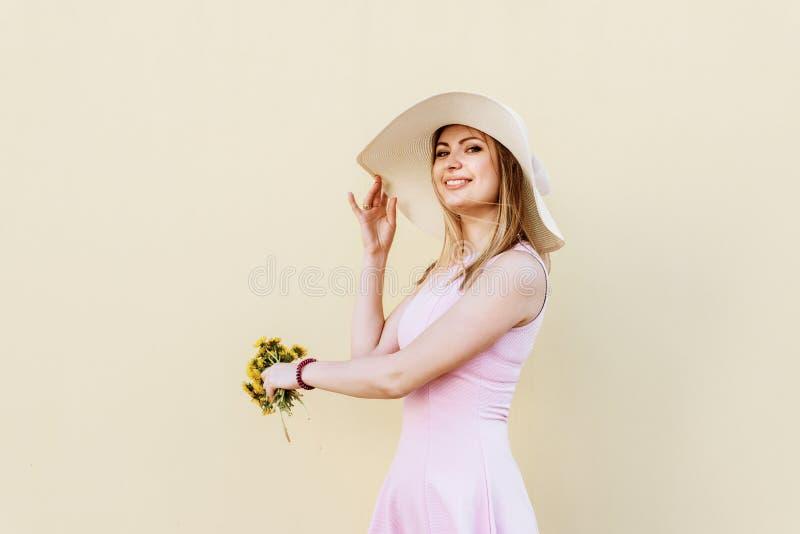 Härlig, älskvärd nätt flicka i en rosa klänning, i le för sugrörhatt som poserar ståenden mot en gul vägg royaltyfri foto
