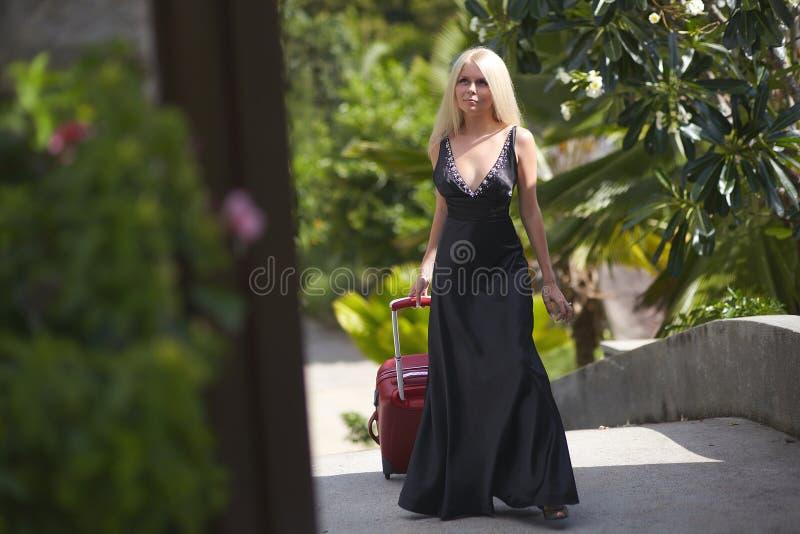 Härlig, älskvärd sexuell flicka som går med bagagepåsen till hotellet royaltyfri fotografi
