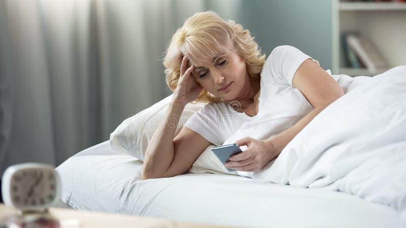 Härlig åldrig kvinna som ligger i säng som pratar i sociala nätverk på smartphonen arkivbild