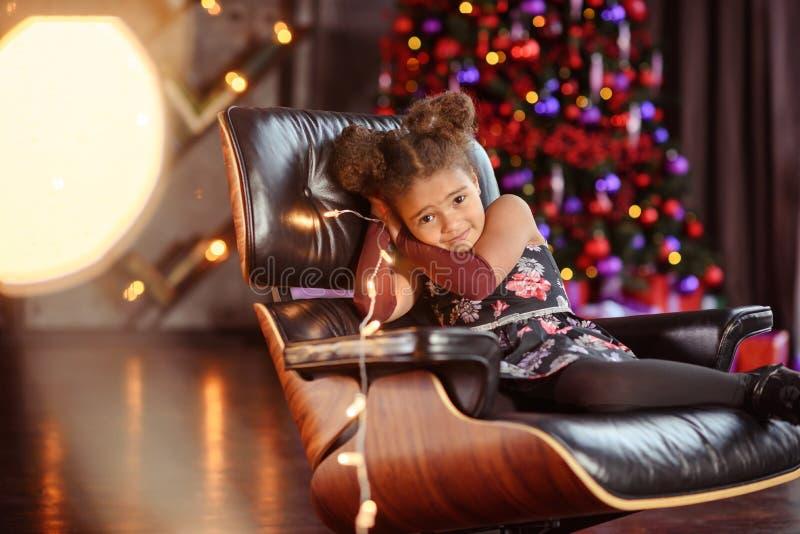 Härlig årig bärande stilfull klänning för ungeflicka som 5-6 sitter i fåtölj över julgranen i rum se kameran ferie royaltyfri fotografi