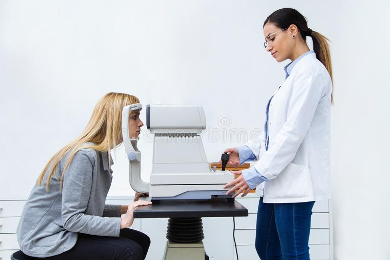 Härlig ögonläkare som gör diagnostik av visionen för kvinnlig patient i ögon- klinik royaltyfria bilder
