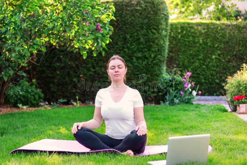 Härlig övande yoga för ung kvinna i trädgård utomhus arkivfoton