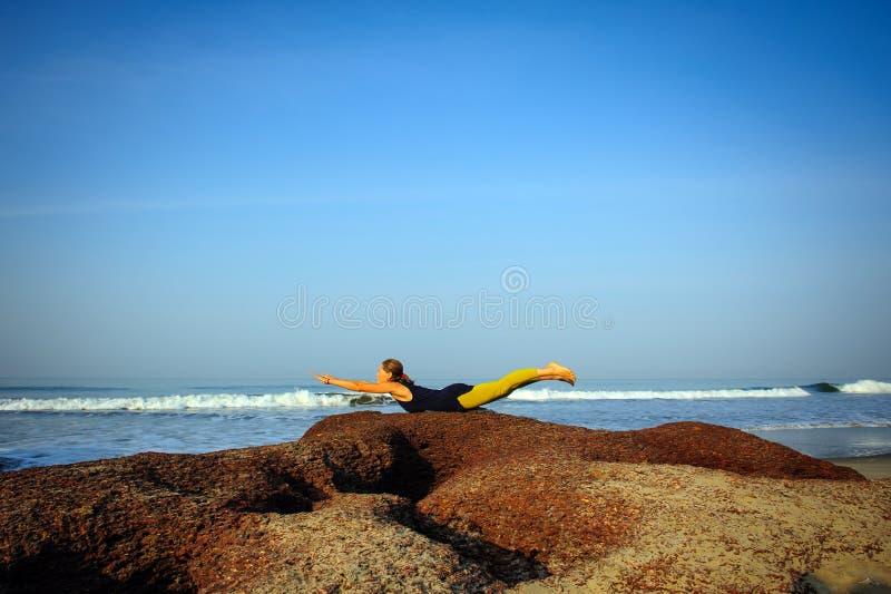 Härlig övande yoga för ung kvinna och sträckningsövningar på sommarhavstranden fotografering för bildbyråer