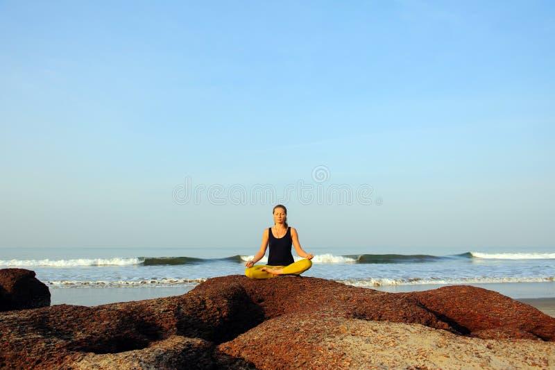 Härlig övande yoga för ung kvinna och sträckningsövningar på sommarhavstranden royaltyfri foto