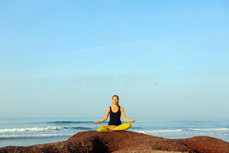 Härlig övande yoga för ung kvinna och sträckningsövningar på sommarhavstranden arkivfoto
