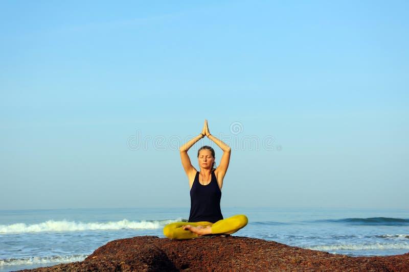 Härlig övande yoga för ung kvinna och sträckningsövningar på sommarhavstranden arkivbilder