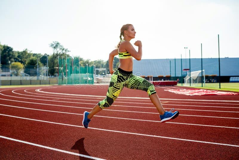 Härlig övning för ung kvinna som joggar och kör på idrotts- spår på stadion arkivbild
