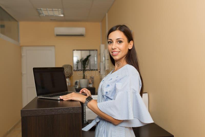 Härlig administratör för ung kvinna på mottagandet som arbetar på bärbara datorn royaltyfria foton