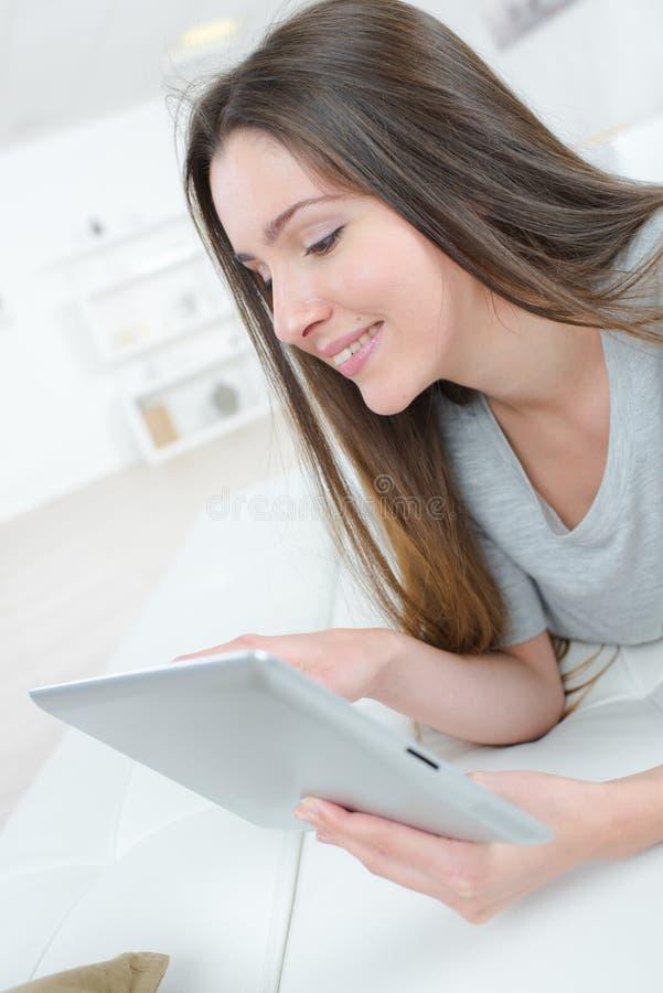Härlig affärsdam som använder den digitala minnestavlan och att le arkivbild