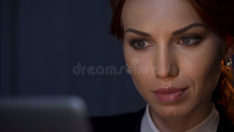 Härlig affärsdam som arbetar på bärbara datorn som ser på skärmen på nattkontoret arkivfoton