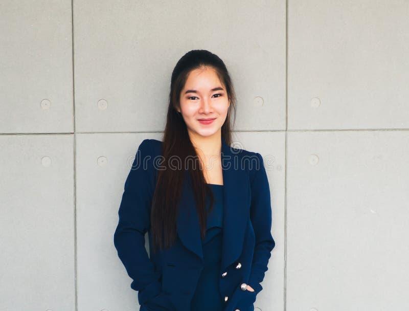 Härlig affärskvinna för asiatiskt långt hår i marinblå dräkt arkivfoto