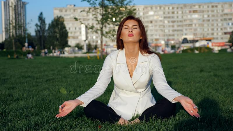 Härlig affärskvinna i den vita dräkten som gör yoga för utomhus- avkoppling royaltyfri foto