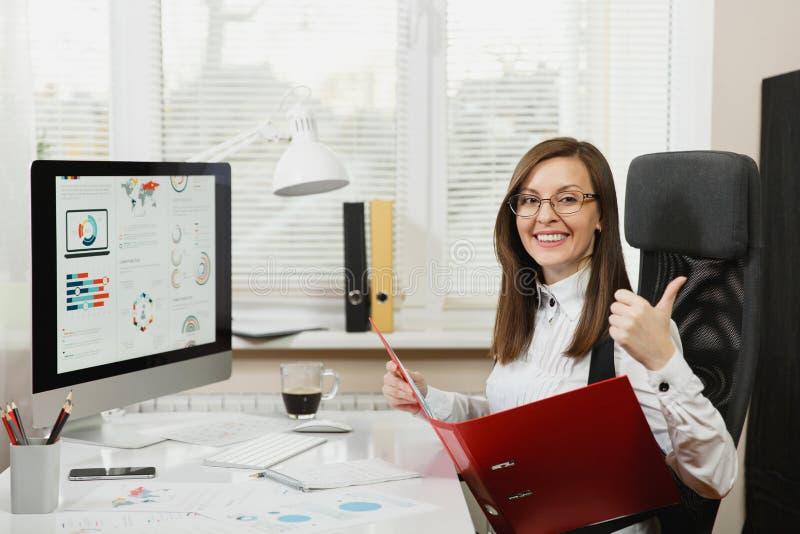 Härlig affärskvinna i dräkt- och exponeringsglasarbete på datoren med dokument i ljust kontor royaltyfria bilder
