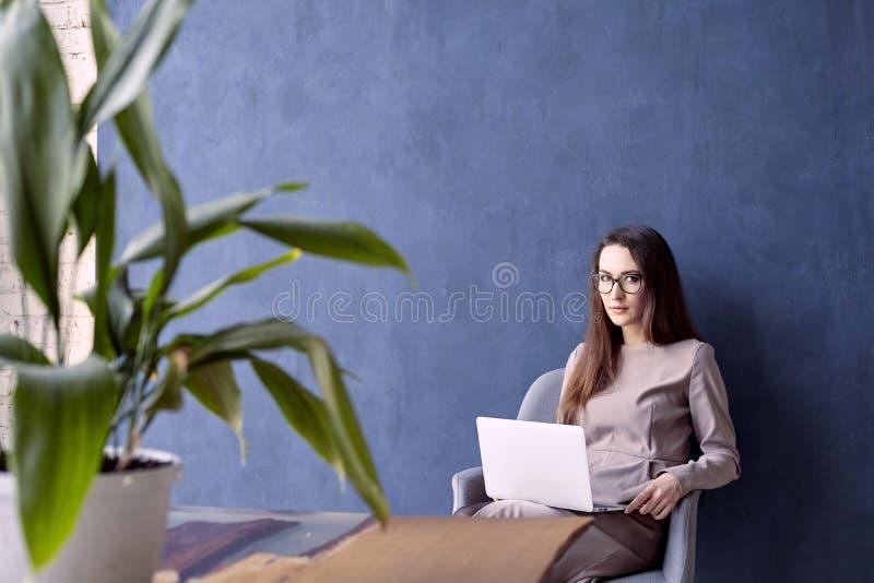 Härlig affärskvinna med långt hår genom att använda den moderna bärbar datordatoren, medan sitta i hans moderna vindkontor royaltyfri fotografi