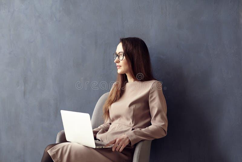 Härlig affärskvinna med långt hår genom att använda den moderna bärbar datordatoren, medan sitta i hans moderna vindkontor royaltyfria bilder