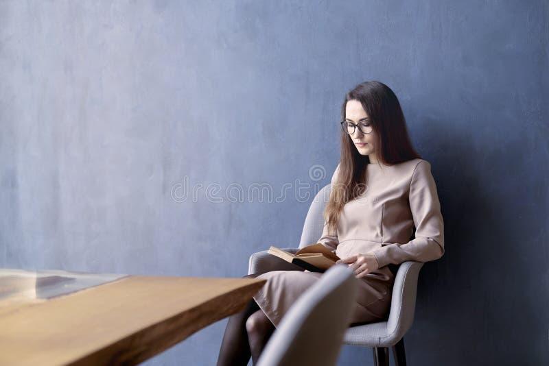 Härlig affärskvinna med långt hår som läser en bok royaltyfria bilder