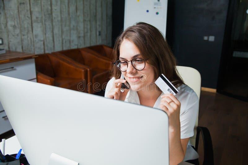 Härlig affärskvinna på kontorskreditkortonline-komrets arkivbilder