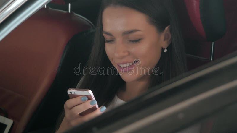 Härlig affärskvinna som överför en text, medan placera i bilen för affärsgrupp med röda stolar, ung studentflicka royaltyfri foto