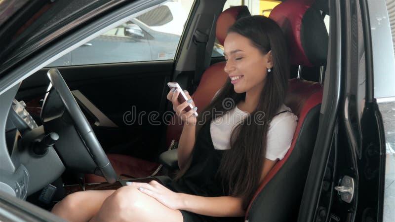 Härlig affärskvinna som överför en text, medan placera i bilen för affärsgrupp med röda stolar, ung studentflicka royaltyfri bild