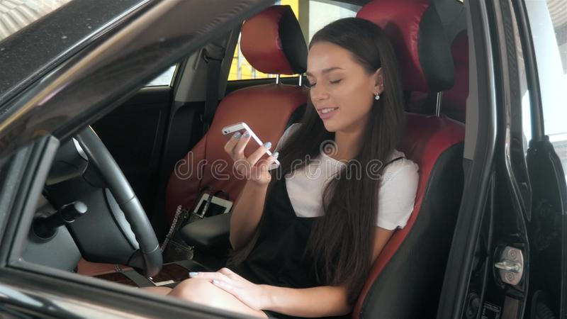 Härlig affärskvinna som överför en text, medan placera i bilen för affärsgrupp med röda stolar, ung studentflicka arkivfoton