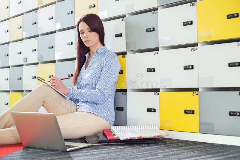Härlig affärskvinna som använder bärbara datorn, medan skriva i omklädningsrum med låsbara skåp royaltyfri fotografi