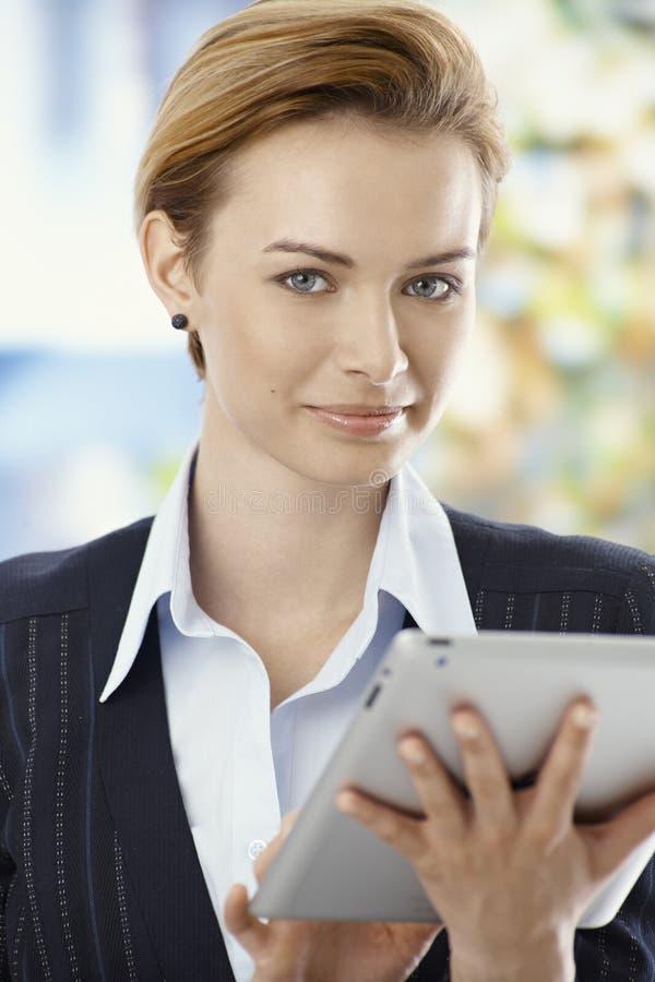 Härlig affärskvinna som använder minnestavlaPC royaltyfri foto