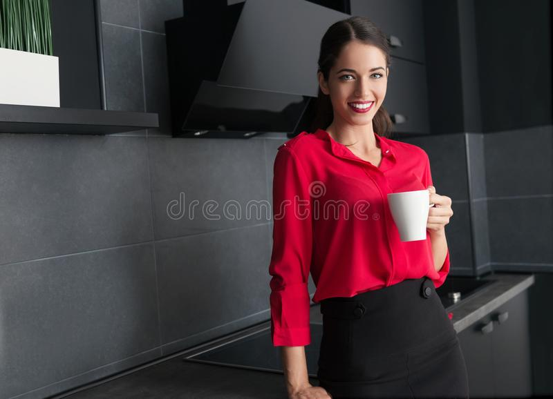 Härlig affärskvinna som dricker kaffe/te i ett modernt kök arkivfoton