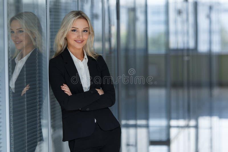 Härlig affärskvinna som i regeringsställning ler med vikta armar arkivbilder