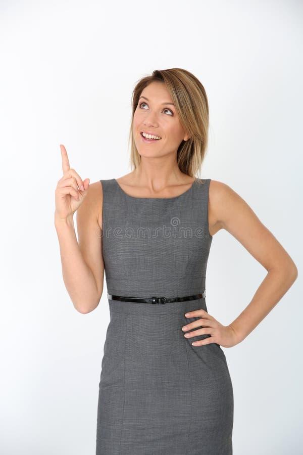 Härlig affärskvinna som pekar upp fingret arkivfoton