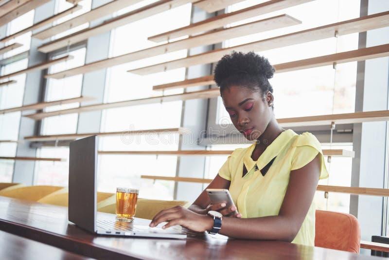 Härlig afrikansk amerikan som arbetar på en bärbar dator i en restaurang En fundersam härlig kvinna, allt in jobbet royaltyfri fotografi