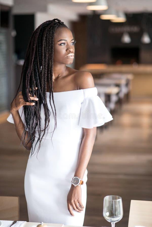 Härlig afrikansk amerikanflicka i en vit klänning som poserar för kamera Dreadlocks eller flätade trådar för afrikan på flicka` s royaltyfri foto