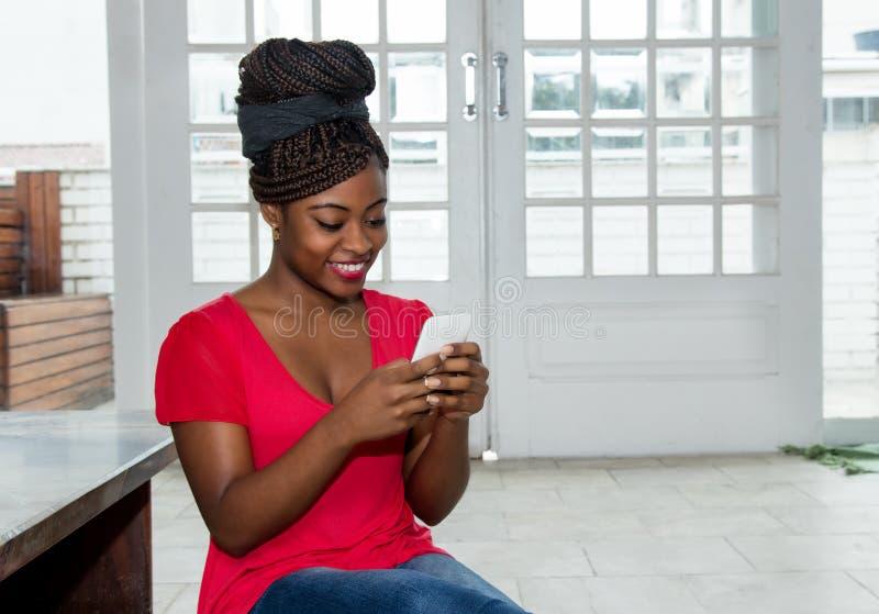Härlig afrikansk amerikankvinna som överför meddelandet med telefonen fotografering för bildbyråer