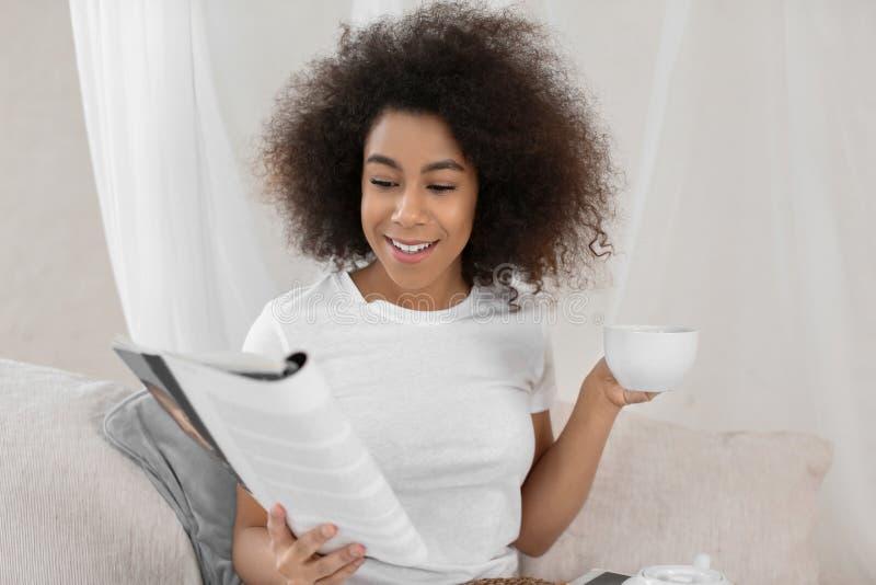 Härlig afrikansk amerikankvinna som dricker te, medan läsa tidskriften hemma royaltyfria bilder