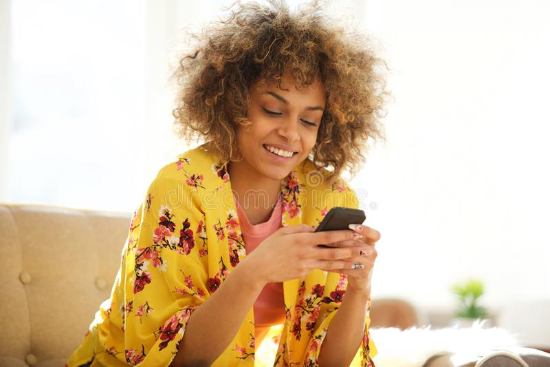 Härlig afrikansk amerikankvinna som hemma använder mobiltelefonen arkivfoto
