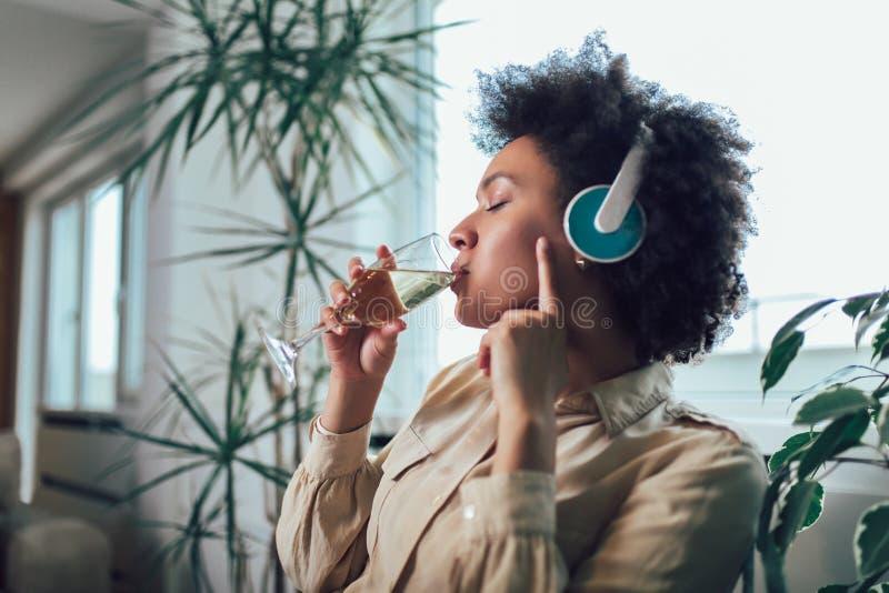 Härlig afrikansk amerikankvinna som kopplar av och lyssnar till musik genom att använda headphonen som dricker vin arkivfoton