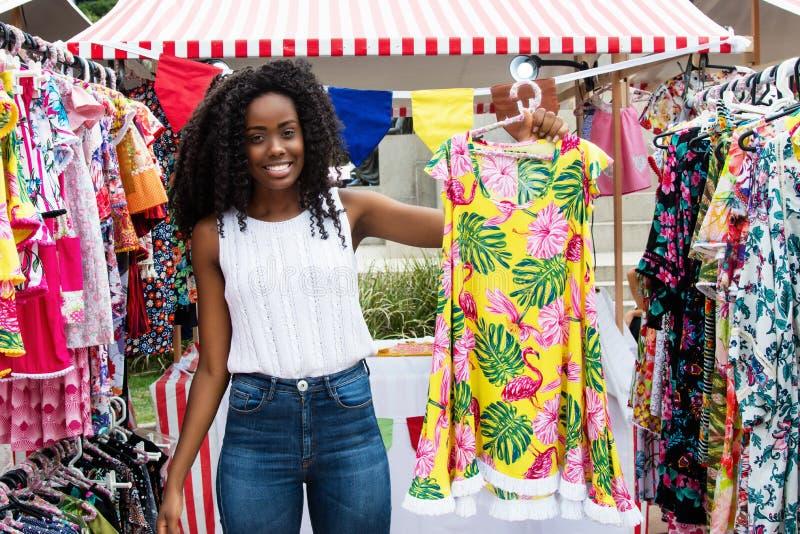 Härlig afrikansk amerikankvinna som säljer kläder på marknaden arkivfoton