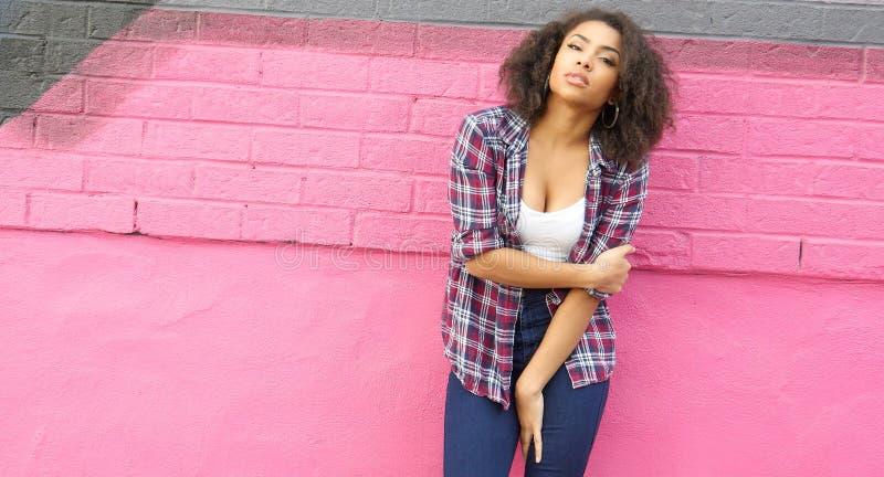 Härlig afrikansk flicka på rosa väggbakgrund i stads- plats royaltyfri fotografi