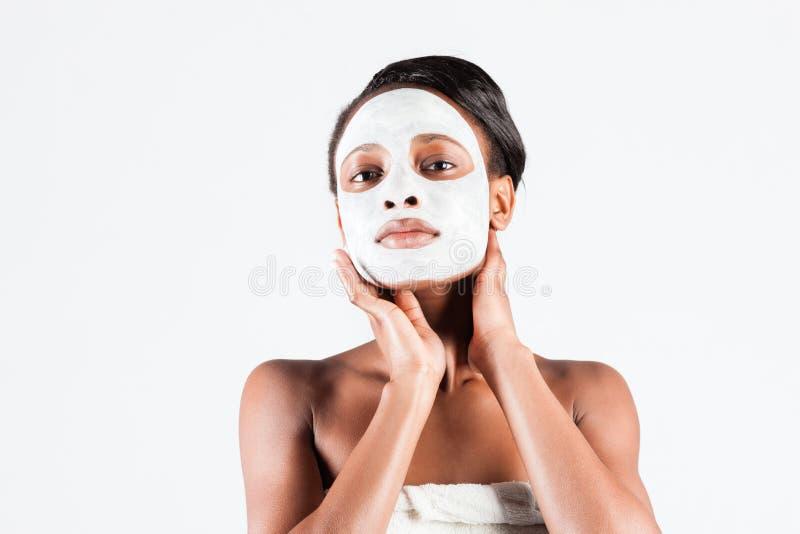 Härlig afrikansk kvinna i studio med den ansikts- maskeringen arkivfoto