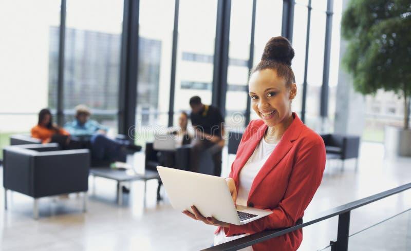 Härlig afrikansk kvinna med bärbara datorn i regeringsställning arkivfoto