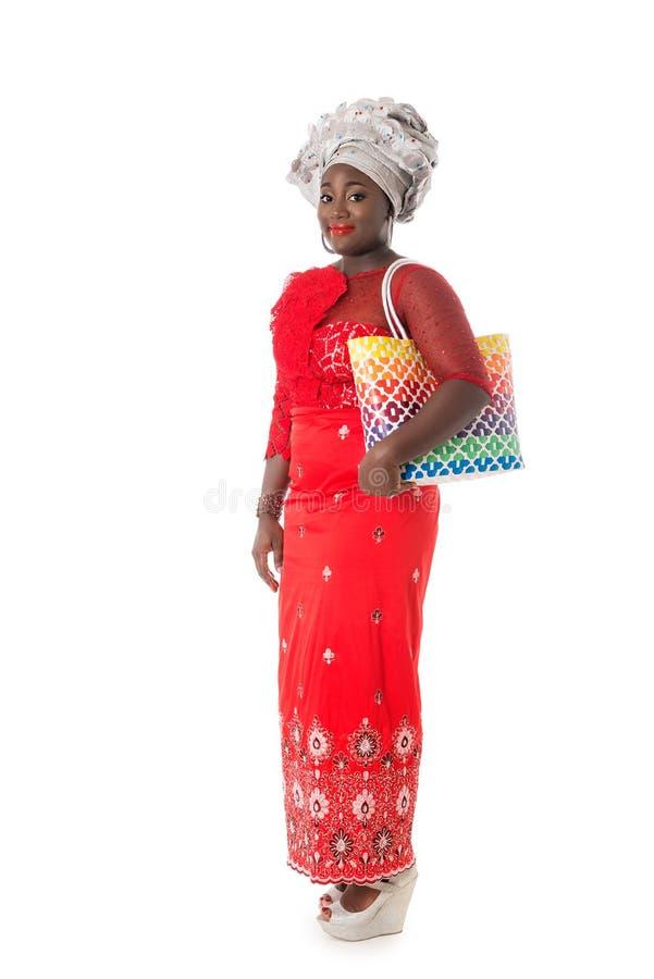 Härlig afrikansk kvinna som går i traditionella röda kläder arkivfoto