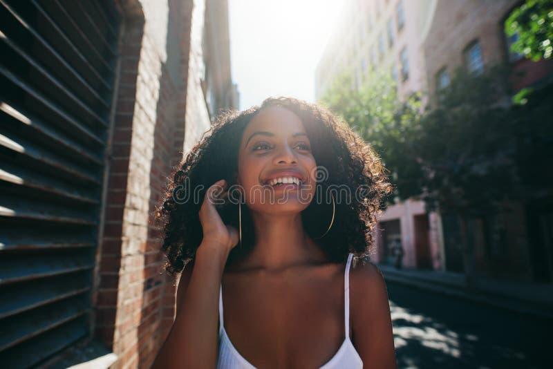 Härlig afrikansk kvinna som går ner stadsgatan arkivfoto