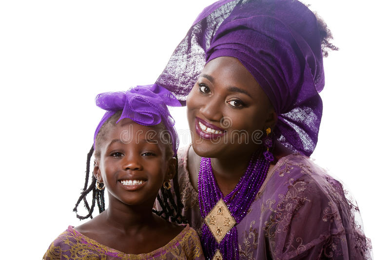 Härlig afrikansk modell i traditionell klänning med den lilla flickan isolerat royaltyfri fotografi