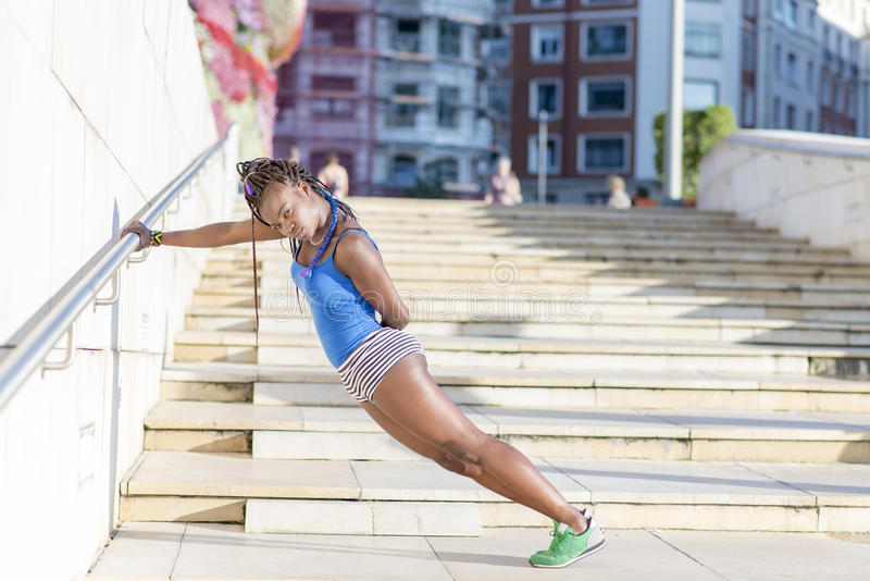 Härlig afrikansk sportkvinna som gör elasticiteter, sunt begrepp arkivfoton